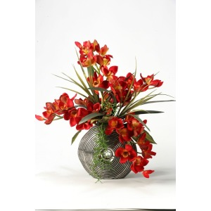 Red cymbidium orchids with foliage and succulents in silver and black ceramic planter
